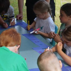 Orange group creating a paper chain of friendship